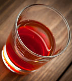 Glass with alcohol costs on a wooden table Stock Photos