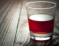 Glass with alcohol costs on a wooden table Stock Photo