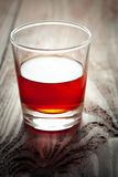 Glass with alcohol costs on a wooden table Royalty Free Stock Photography