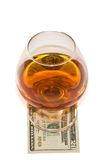 Glass of alcohol with dollar Royalty Free Stock Photos