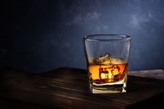 Glass of alcohol drink with ice on wooden table stock photos