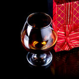 Glass with alcohol and a gift. Stock Image