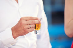 Glass of alcohol in hands Stock Photography