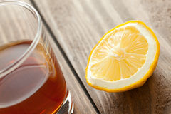 Glass with alcohol and a lemon costs on a wooden table Stock Photos