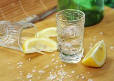 Glass of alcohol and lemon Royalty Free Stock Images