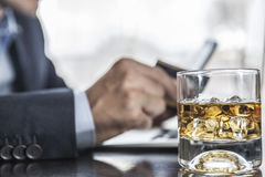 Glass Of Alcohol. Man holding a card and phone with a glass of alcohol near him royalty free stock images