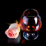 Glass with alcohol and rose. Royalty Free Stock Photography