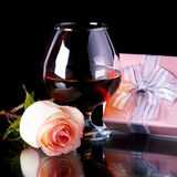 Glass with alcohol and rose and gift box. Glass and rose and gift box. Alcohol and flower and gift. Glass with drink and a pink rose and gift Royalty Free Stock Images