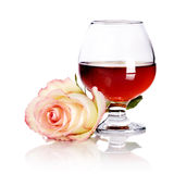 Glass with alcohol and rose on a white background. Royalty Free Stock Photo