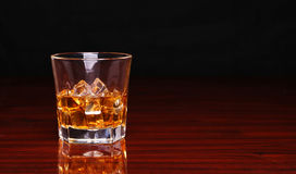 Glass of alcohol scotch whiskey with ice cube on wooden table Royalty Free Stock Image