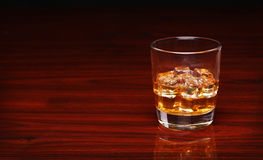 Glass of alcohol scotch whiskey with ice cube on wooden table Stock Photo
