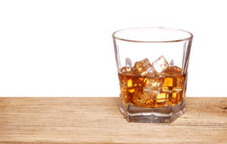 Glass of alcohol scotch whiskey with ice cube on wooden table Royalty Free Stock Photography