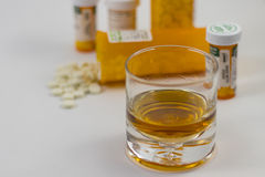 A glass of alcohol and several bottles of Pharmaceuticals Stock Photography