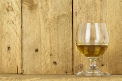 Glass of alcohol. Shown on the background of stained wood Stock Images