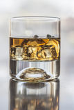 Glass Of Alcohol. A glass of alcohol on table with reflection stock photos