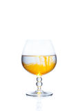 A glass with alcohol. On the white background.  The liquid of the glass is orange. The object is completely isolated Stock Photo