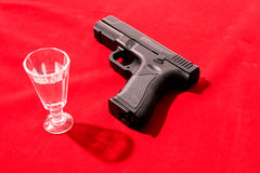 Glass of alcoholic drink and gun Royalty Free Stock Images