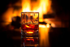 Glass alcoholic drink wine in front warm fireplace. Royalty Free Stock Image