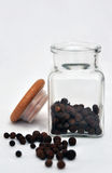 Glass of allspice. Opened glass dose with allspice against white background Stock Photography