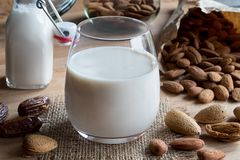 A glass of almond milk with unshelled and shelled almonds. A glass of almond milk on a wooden table, with shelled, unshelled and soaked almonds and dates in the Stock Photos