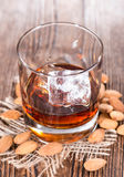 Glass with Amaretto and Ice. Cubes on dark background with some almonds stock photos