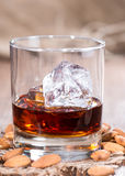 Glass with Amaretto and Ice. Cubes on dark background with some almonds royalty free stock photo