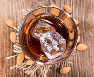 Glass with Amaretto and Ice. Cubes on dark background with some almonds royalty free stock photography