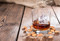 Glass with Amaretto and Ice. Cubes on dark background with some almonds stock photography