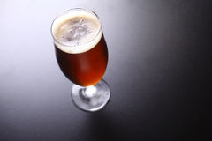Glass of amber ale. Tall tulip glass of amber ale over a dark background Stock Photo