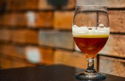 Glass of amber Pale Ale beer on wooden table in bar on brick wall background with copy space. Close up on a glass of amber Pale Ale beer on wooden table in bar stock photo