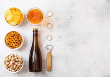 Glass And Bottle Of Craft Lager Beer With Snack And Opener On Stone Kitchen Table Background. Pretzel And Crisps And Pistachio In Stock Photo