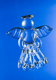 Glass angel. Figurine of glass angel isolated on blue background stock images