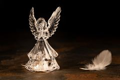 Glass angel on a dark background. Glass angel with fallen feathers on a dark background stock image