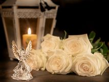 Glass angel on a dark background. Glass angel with fallen feathers, roses and candle on a dark background royalty free stock photography