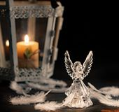 Glass angel on a dark background. Glass angel with fallen feathers and candle on a dark background royalty free stock photo