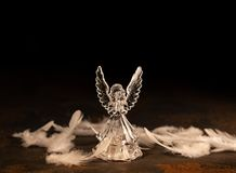 Glass angel on a dark background. Glass angel with fallen feathers on a dark background royalty free stock photo
