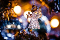Glass Angel figurine with Bokeh. A glass angel figurine at the center of an illuminating bokeh of lights royalty free stock images