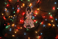 Glass angel with garland. Glass garland angel Christmas lights stock photo
