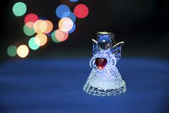 Glass angel holding heart. On dark blurry background stock photos