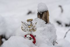 Christmas ornaments in snow. A glass angel holding a star outdoors in the snow with tree backdrop setting the mood for Christmas stock photography