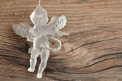 A glass angel. Isolated on a wooden background stock photo