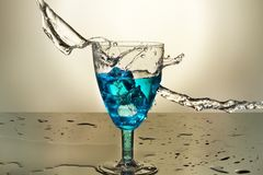 A glass of Anise hit by a wave of liquid. A crystal blue glass with anise and cubes of clown with white background on black table stock photos