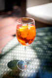 Glass of Aperol Spritz. Cocktail on the glass table in outdoor resort bar Stock Images