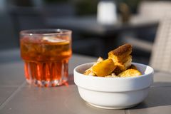 Glass red aperitif and bowl of toast in bar stock photo