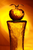 Glass apple. On broken cylinder in yellow light Royalty Free Stock Image
