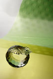 Glass apple. Glass crystal apple on plastic green background Stock Photo
