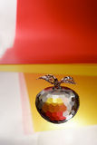 Glass apple. Glass crystal apple on red and yellow plastic background Stock Photos