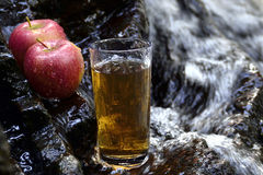 Glass of apple juice. Apple  juice and two apples by the waterfall Stock Photo