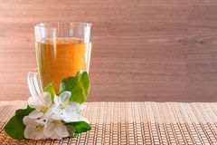 A glass of apple juice and apple-tree flowers on a wooden background. Stock Image