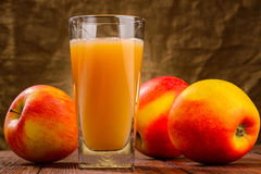 Glass of apple juice with apples on fabric Royalty Free Stock Photo